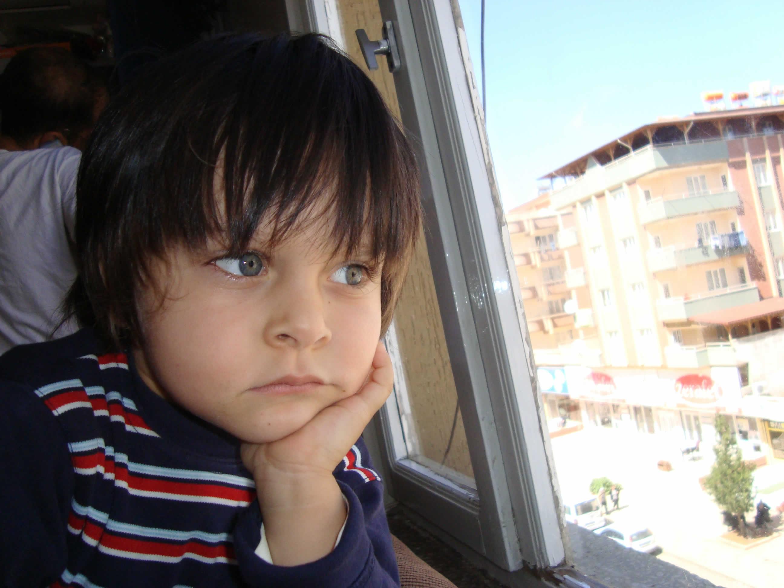 camdan dışarı bakan çocuk